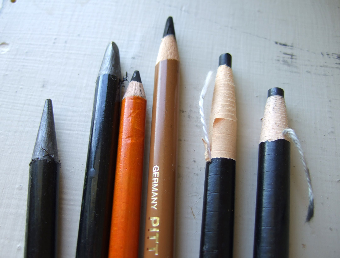 "Two ""woodless"" graphite pencils, two charcoal pencils, and two grease pencils"